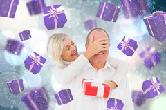 Composite image of woman surprising man with gift Stock Image