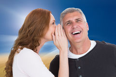 Composite image of woman telling secret to her partner Stock Photography