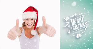 Composite image of woman with the thumbs up and a christmas hat Stock Image