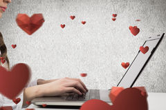 Composite image of woman typing on her laptop Royalty Free Stock Photography