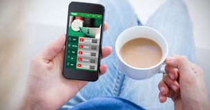 Composite image of woman using her mobile phone and holding cup of coffee Royalty Free Stock Photos
