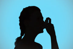 Composite image of woman using inhaler for asthma Royalty Free Stock Image