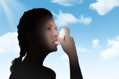 Composite image of woman using inhaler for asthma Stock Photos