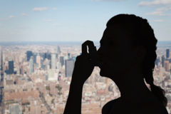 Composite image of woman using inhaler for asthma Stock Photo