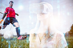 Composite image of woman using an oculus. Woman using an oculus against goalkeeper in red kicking ball away from goal royalty free stock image