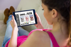 Composite image of woman using tablet at home Royalty Free Stock Image