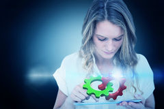 Composite image of woman using tablet pc Stock Photography