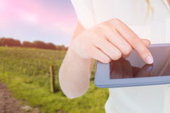 Composite image of woman using tablet pc against rural landscape Stock Images