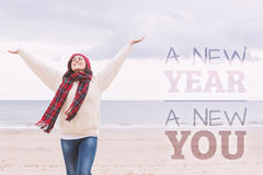 Composite image of woman in warm clothing stretching arms on beach Stock Photo