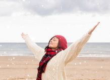 Composite image of woman in warm clothing stretching arms at beach Royalty Free Stock Photo
