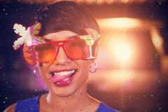 Composite image of woman wearing fancy sunglasses making funny faces in bar Royalty Free Stock Image