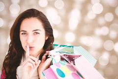 Composite image of woman wearing a scarf and holding shopping bags Stock Image