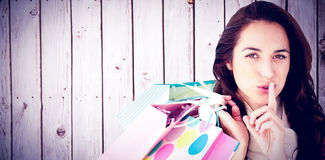 Composite image of woman wearing a scarf and holding shopping bags Stock Photos