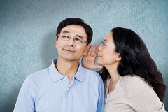 Composite image of woman whispering into partners ear Royalty Free Stock Photography