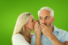 Composite image of woman whispering a secret to husband Stock Images