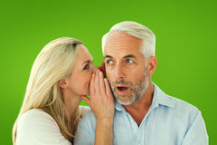 Composite image of woman whispering a secret to husband Royalty Free Stock Photo