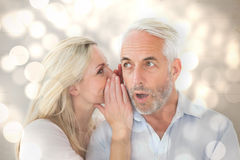 Composite image of woman whispering a secret to husband Stock Image