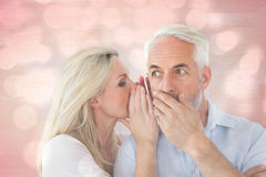 Composite image of woman whispering a secret to husband Royalty Free Stock Photos