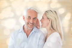 Composite image of woman whispering a secret to husband Stock Photo
