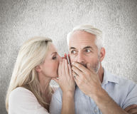 Composite image of woman whispering a secret to husband Royalty Free Stock Photography