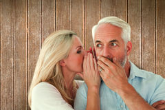 Composite image of woman whispering a secret to husband Royalty Free Stock Images