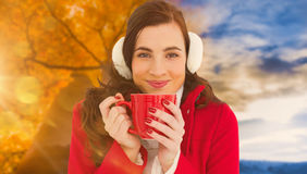 Composite image of woman in winter clothes enjoying a hot drink Stock Images