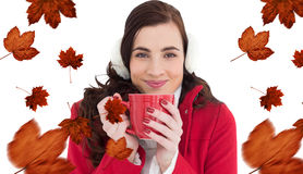 Composite image of woman in winter clothes enjoying a hot drink Stock Photography