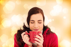 Composite image of woman in winter clothes enjoying a hot drink eyes closed Stock Photos