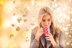 Composite image of woman in winter clothes holding a mug stock image