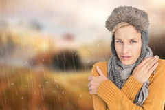Composite image of woman in winter clothes shivering over white background Stock Photography