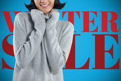 Composite image of woman in winter clothing posing against white background. Woman in winter clothing posing against white background against blue background royalty free stock photography