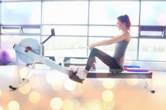 Composite image of woman working out on row machine Stock Photo
