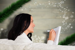 Composite image of woman writing down some notes Stock Image