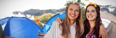 Composite image of women arm in arm with flower crown. Women arm in arm with flower crown against empty campsite at music festival Stock Photos
