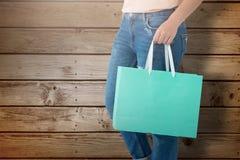 Composite image of women holding shopping bag. Women holding shopping bag against wooden planks background stock image