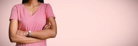 Composite image of women in pink for breast cancer focus on crossed arms stock images