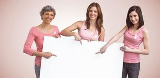 Composite image of women in pink outfits holding board for breast cancer awareness Royalty Free Stock Photography