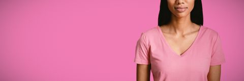 Composite image of women in pink standing for breast cancer royalty free stock photography