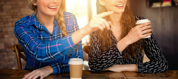 Composite image of women pointing forward in cafe Royalty Free Stock Image