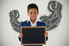 Composite image of work tool against white background. Work tool against white background against schoolboy holding blank writing slate against white background Stock Photography