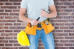 Composite image of worker holding hammer over white background Royalty Free Stock Images