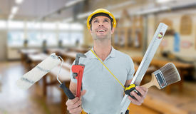 Composite image of worker holding various equipment over white background Stock Photos