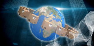 Composite image of world map amidst cardboard boxes Stock Photo