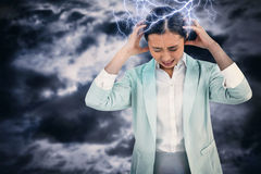 Composite image of worried businesswoman holding her head Royalty Free Stock Photo