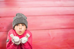 Composite image of wrapped up little girl blowing over hands Stock Photo