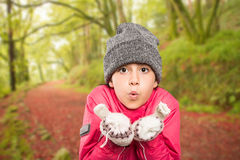 Composite image of wrapped up little girl blowing over hands Royalty Free Stock Photo