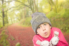 Composite image of wrapped up little girl blowing over hands Royalty Free Stock Image
