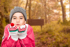 Composite image of wrapped up little girl blowing over hands Stock Image