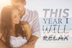 Composite image of this year i will relax. This year i will relax against attractive couple cuddling royalty free stock images