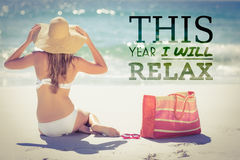 Composite image of this year i will relax. This year i will relax against rear view of blonde in swimsuit sitting at beach Royalty Free Stock Image